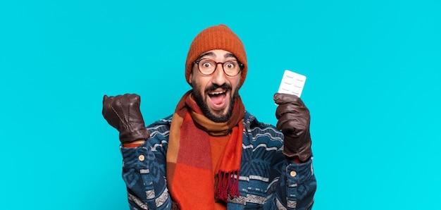 젊은 미친 수염 남자. 승자처럼 승리를 축하하고 겨울 옷을 입고. 질병 개념