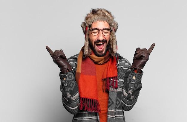젊은 미친 수염된 남자. 승자처럼 승리를 축하하고 겨울 옷을 입고