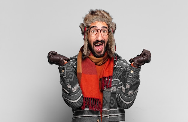 젊은 미친 수염 남자. 승자처럼 승리를 축하하고 겨울 옷을 입고