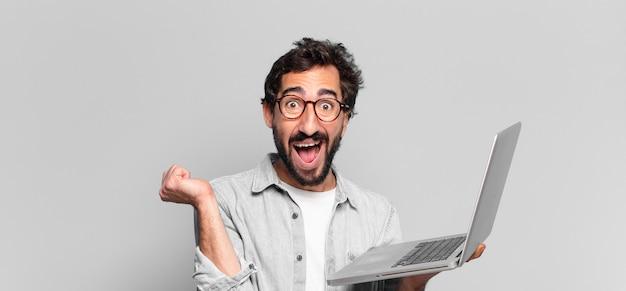 若い狂ったひげを生やした男。勝者のように勝利を祝う。ノートパソコンのコンセプト