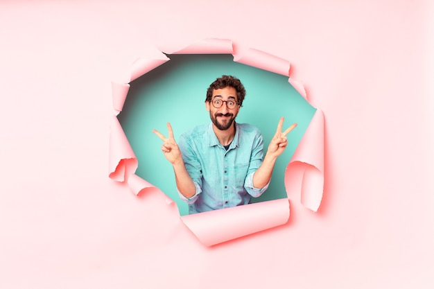 Young crazy bearded man. celebrating a triumph like a winner. paper hole empty background concept