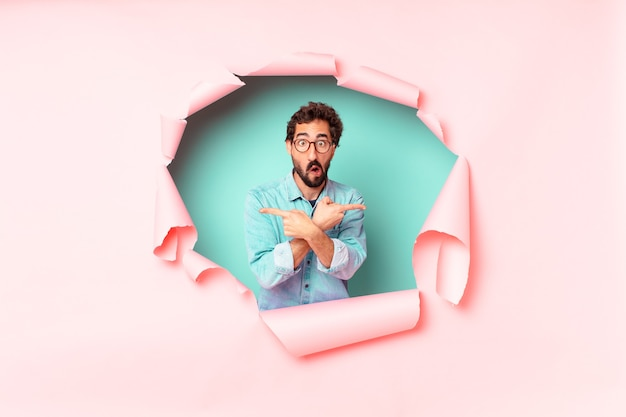Young crazy bearded man confused. paper hole empty background concept
