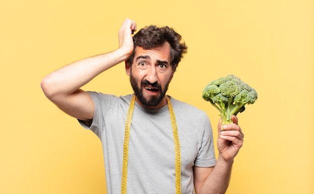 Young crazy bearded man dieting angry expression and holding a cabbage