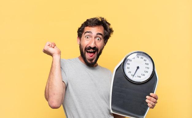 Молодой сумасшедший бородатый мужчина сидит на диете, празднует успешную победу и держит весы