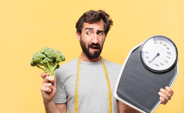 疑わしいまたは不確かな表現をダイエットし、体重計を保持している若い狂ったひげを生やした男