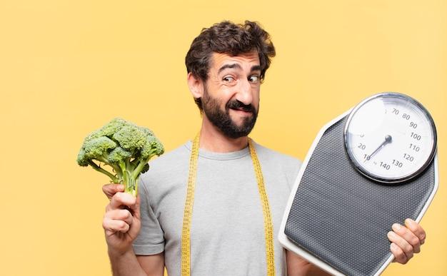 Молодой сумасшедший бородатый мужчина сидит на диете с сомнением или неуверенным выражением лица и держит весы