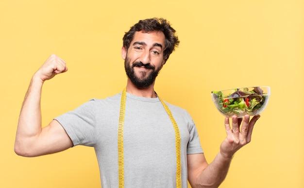 Молодой сумасшедший бородатый мужчина сидит на диете со счастливым выражением лица и держит салат
