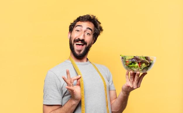 행복한 표정으로 다이어트를 하고 샐러드를 들고 있는 미친 수염 난 남자