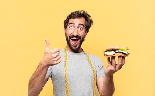 Молодой сумасшедший бородатый мужчина сидит на диете со счастливым выражением лица и держит бутерброд