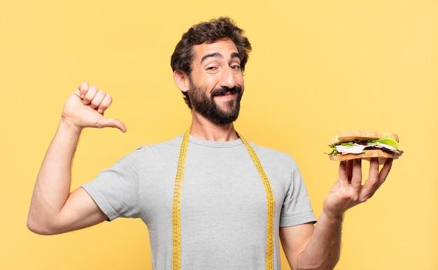 행복한 표정으로 다이어트를 하고 샌드위치를 든 젊은 미친 수염 난 남자