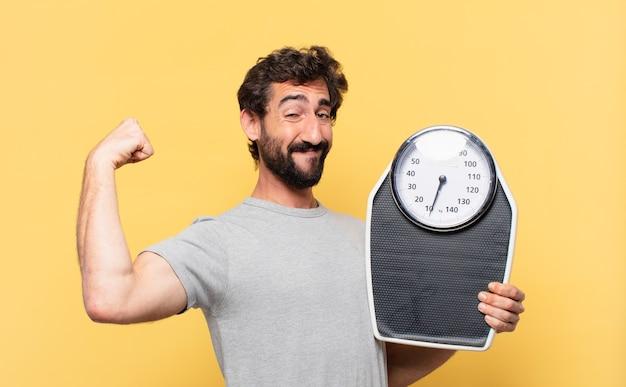 Молодой сумасшедший бородатый мужчина сидит на диете со счастливым выражением лица и держит весы