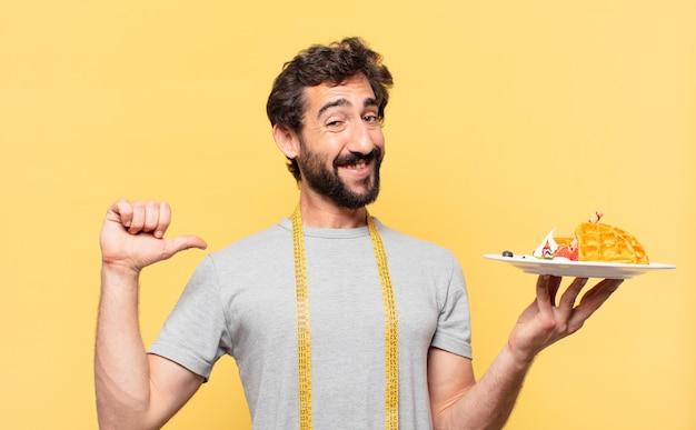 Молодой сумасшедший бородатый мужчина сидит на диете со счастливым выражением лица и держит вафли