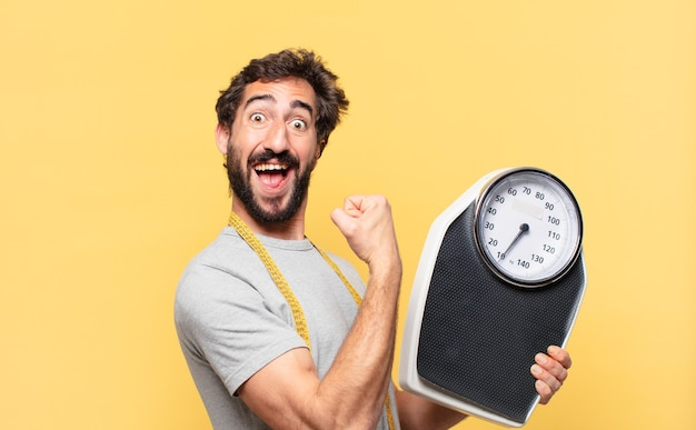 Young crazy bearded man dieting happy expression and holding a sweight scale