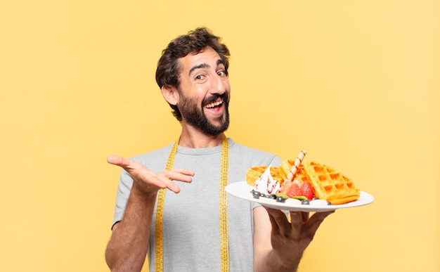 Young crazy bearded man dieting happy expression and holding waffles