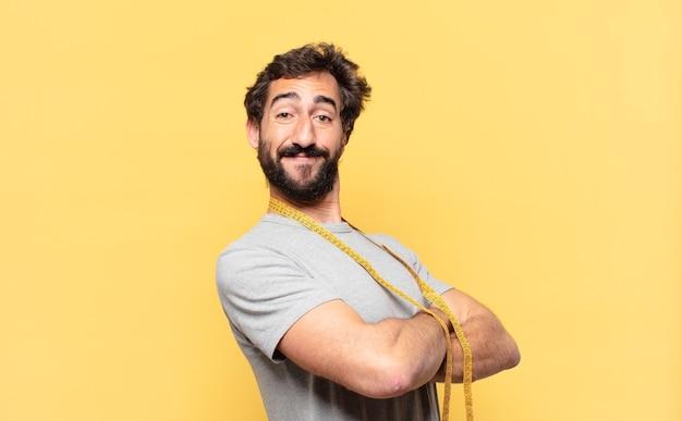 Молодой сумасшедший бородатый мужчина сидит на диете счастливым выражением лица