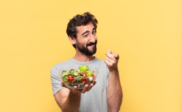 Молодой сумасшедший бородатый мужчина сидит на диете, указывая или показывает и держит салат
