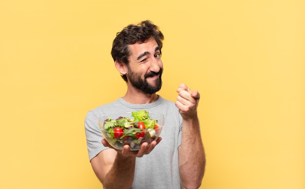Young crazy bearded man dieting pointing or showing and holding a salad