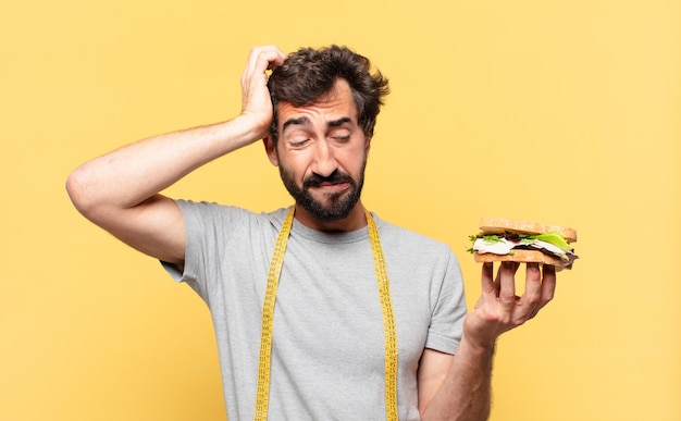 Молодой сумасшедший бородатый мужчина сидит на диете с грустным выражением лица и держит бутерброд