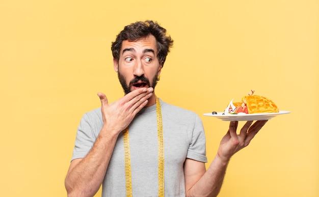 겁 먹은 표정으로 다이어트를 하고 와플을 들고 있는 젊은 미친 수염 난 남자