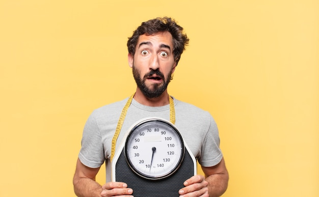 Young crazy bearded man dieting scared expression and holding a sweight scale