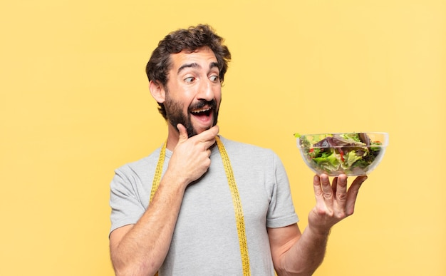 Молодой сумасшедший бородатый мужчина сидит на диете с удивленным выражением лица и держит салат