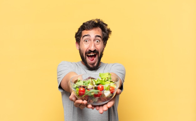 놀란 표정으로 다이어트를 하고 샐러드를 들고 있는 젊은 미친 수염 난 남자