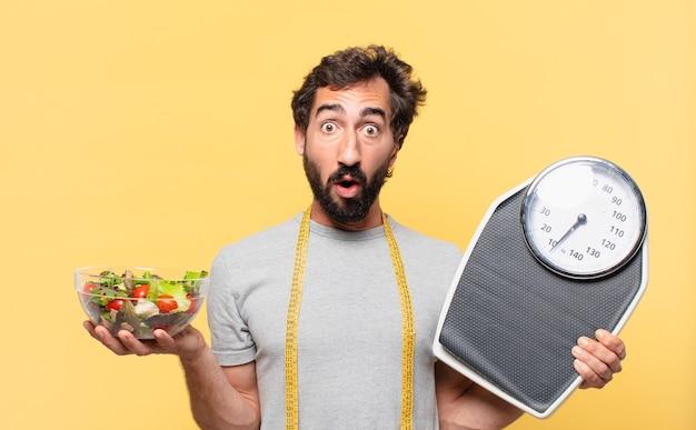 Молодой сумасшедший бородатый мужчина сидит на диете с удивленным выражением лица и держит весы и салат