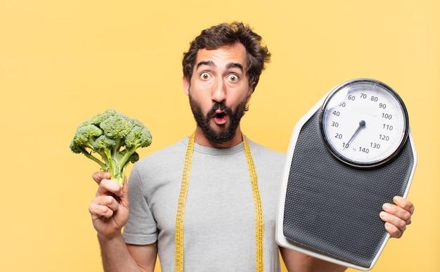 놀란 표정으로 다이어트를 하고 체중계를 들고 있는 젊은 미친 수염 난 남자