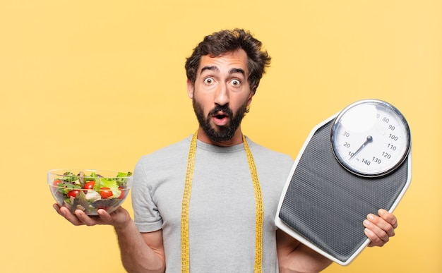 Young crazy bearded man dieting surprised expression and holding a scale and a salad