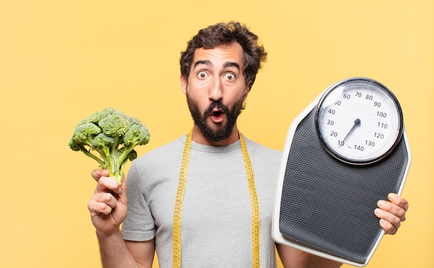 Young crazy bearded man dieting surprised expression and holding a scale