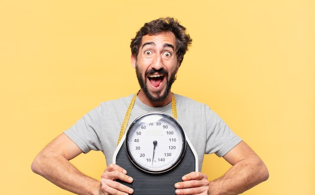 Young crazy bearded man dieting surprised expression and holding a sweight scale