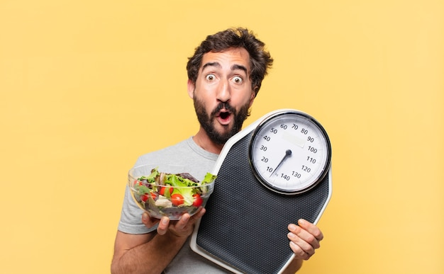 Young crazy bearded man dieting surprised expression and holding a weight scale and a salad