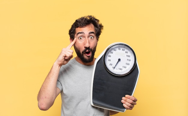 Young crazy bearded man dieting surprised expression and holding a weight scale