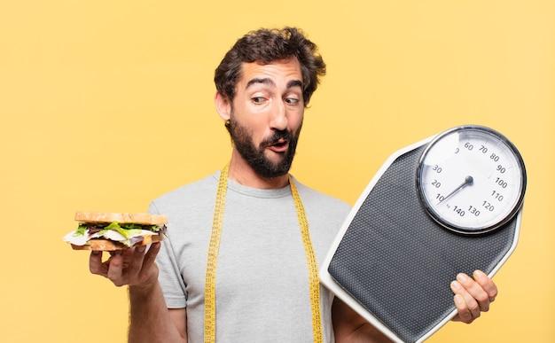 Молодой сумасшедший бородатый мужчина сидит на диете, мышление и держит в руках весы и бутерброд