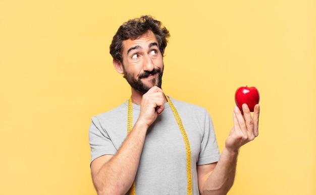 Молодой сумасшедший бородатый мужчина сидит на диете, мышление и держит яблоко
