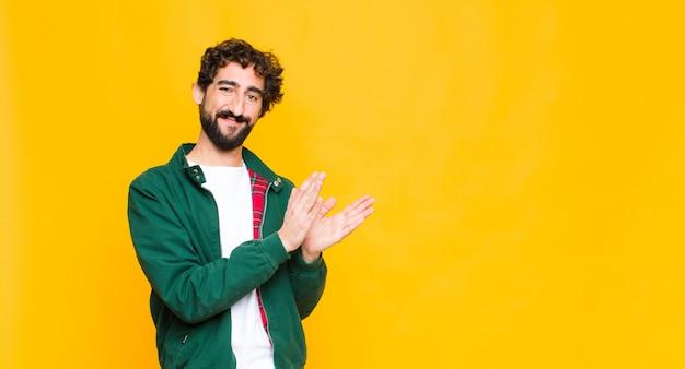 若いクレイジーひげを生やした男は幸せと成功を感じて、笑顔と手をたたいて、平らな壁に対する拍手でおめでとうと言って