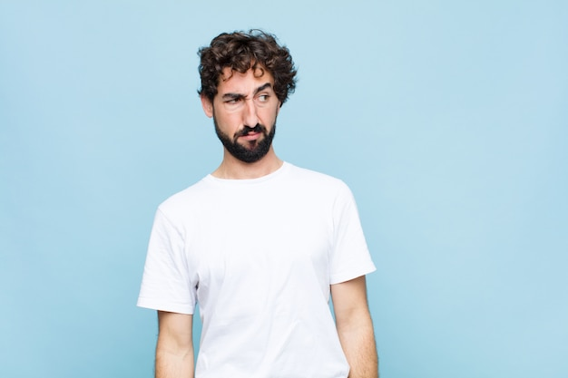 Young crazy bearded man feeling sad, upset or angry and looking to the side with a negative attitude, frowning in disagreement against flat wall