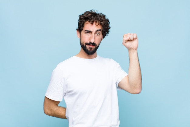 Young crazy bearded man feeling serious, strong and rebellious, raising fist up, protesting or fighting for revolution on flat wall