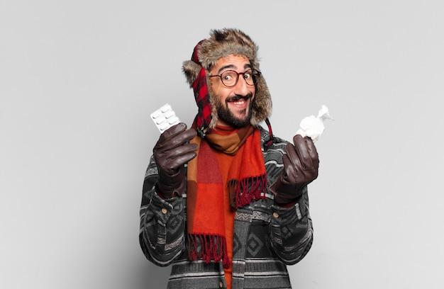 젊은 미친 수염 남자. 행복하고 놀란 표정과 겨울 옷을 입고. 질병 개념