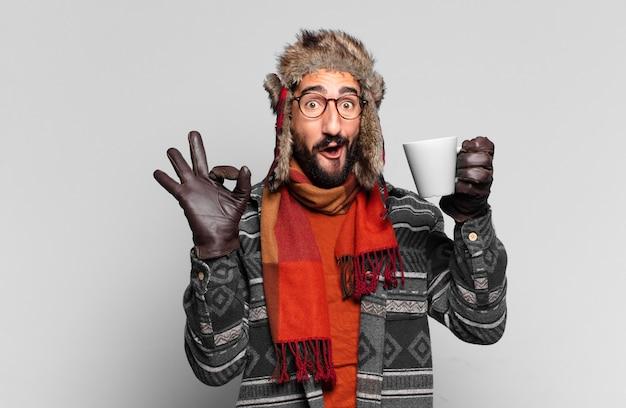 젊은 미친 수염된 남자. 행복하고 놀란 표정과 겨울 옷을 입고
