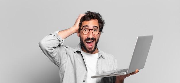 젊은 미친 수염 남자. 행복하고 놀란 표정. 노트북 개념