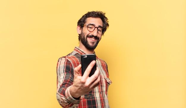 狂ったひげを生やした若い男の幸せな表情と電話を保持