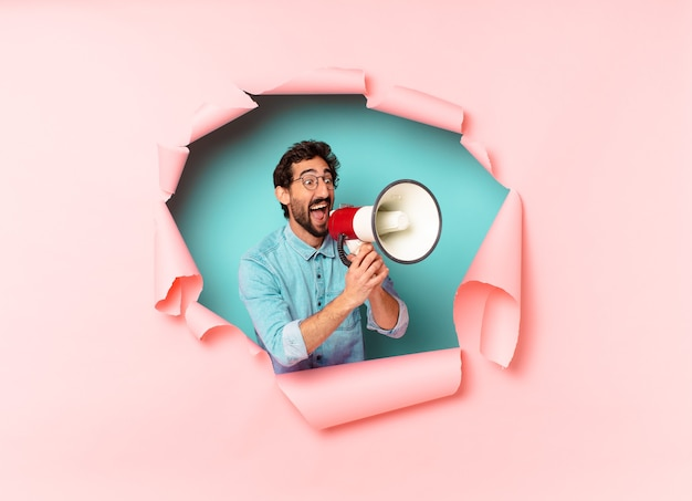 Young crazy bearded man. happy and surprised expression. megaphone concept