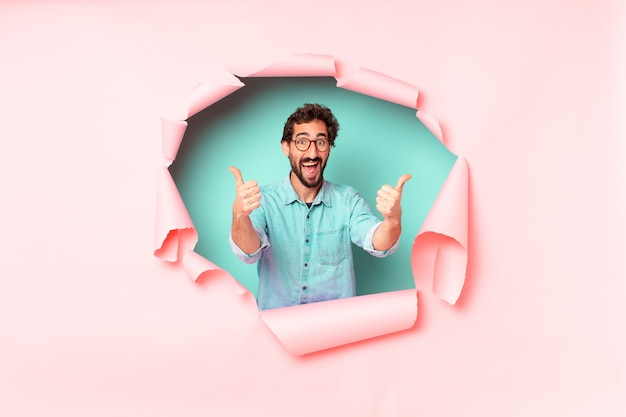 Young crazy bearded man. happy and surprised expression. paper hole empty background concept