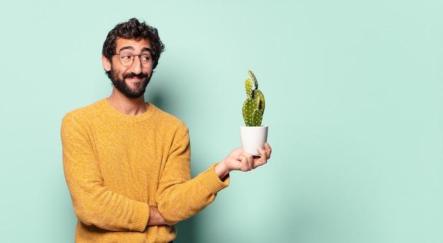 Молодой сумасшедший бородатый мужчина держит домашнее растение кактус