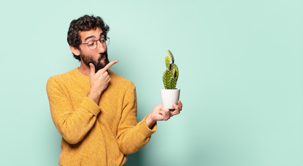 サボテン観葉植物を保持している若い狂ったひげを生やした男