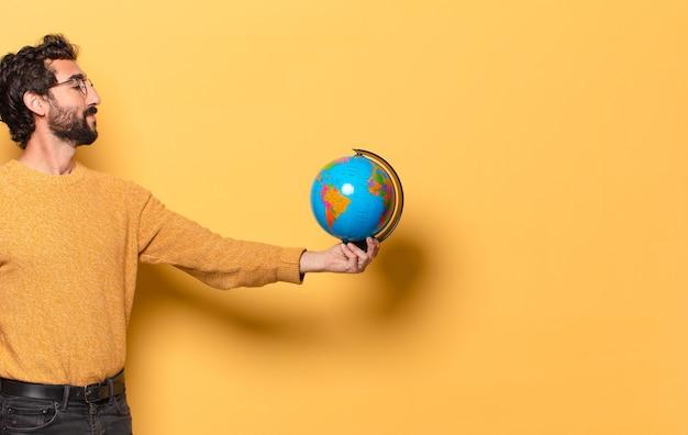 世界の地球地図を持っている若い狂ったひげを生やした男