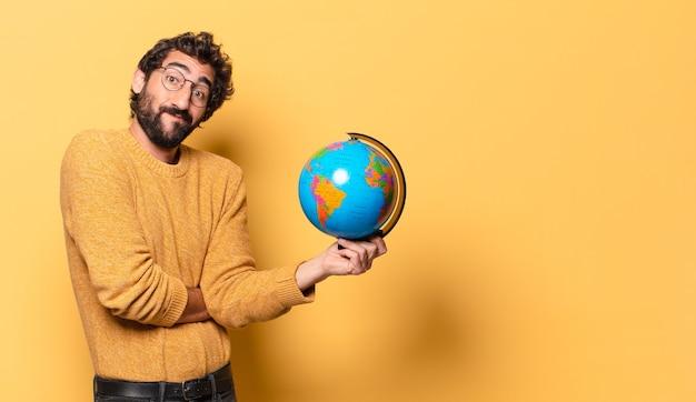 世界の地球地図を持っている若い狂ったひげを生やした男。