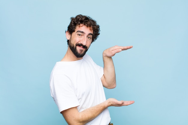 Young crazy bearded man holding an object with both hands on side copy space, showing, offering or advertising an object against flat wall