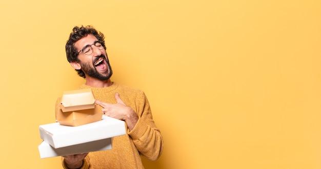 Молодой сумасшедший бородатый мужчина держит фаст-фуд на вынос